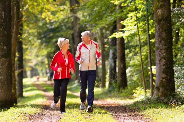 17798709 - senior couple doing sport outdoors, jogging on a forest road in the autumn